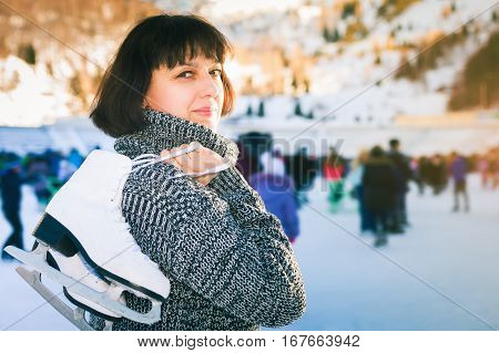 Happy mature woman holds skates at Medeo ice rink. Mother has winter ice skating activities. Almaty