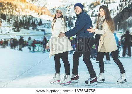 Image of group funny teenagers girls and boy ice skating outdoor at ice rink, looking at camera. Medeo stadium. Almaty. Winter activities for good mood and healthy mind. Healthy lifestyle and sport