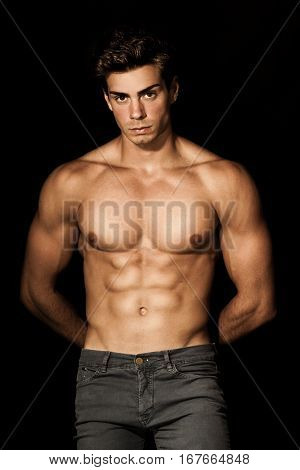 Italian model muscular man. A young Italian boy shirtless posing on a black background. Muscular and athletic. Well-defined muscles.