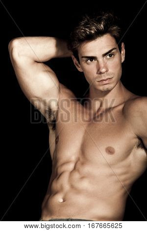 Sexy young man shirtless. Gym muscular body. A sexy young italian man is posing shirtless. He has a hand behind his head. Muscular body, hes a well-defined.