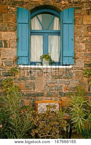 Vintage blue window with shutters on old stone wall and flowers, Crete, Greece. Vintage toned image