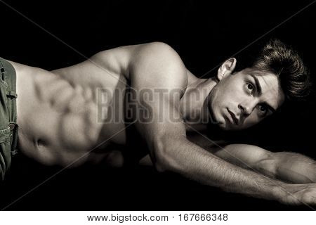 Sexy young man shirtless lying on the ground. Gym muscular body. A sexy young italian man is posing shirtless lying on the ground. Muscular body, hes a well-defined. Almost black and white.