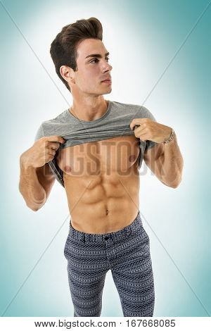 Man athletic with gray t-shirt showing abs. A handsome boy is showing his abs by lifting his shirt. He wears fancy pants and grey t-shirt. He has a physical sculptural and athletic. Hair fashion. On gradient White-Light Blue