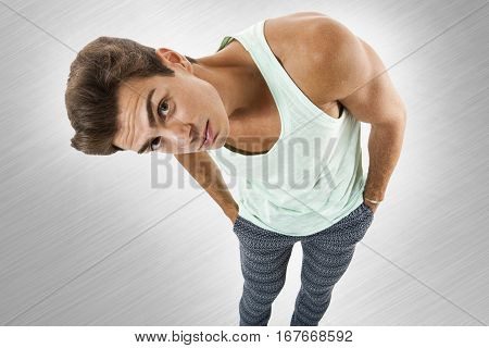 Young model man looking with curiosity from the top isolated. Raised eyebrows and hands in his pockets. Gray gradient background.