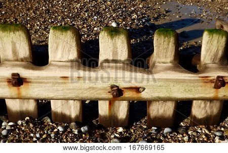 Rust stained wooden beach revetments on shingle beach