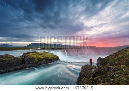 Godafoss waterfall. Beautiful landscape in Iceland. Man in red jacket standing on the rock and looking at the dawn