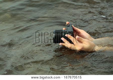 Female hands hold modern black digital camera or digicam over sea or ocean water surface outdoors on grey background