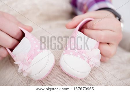 pink booties for newborn baby in hands of  father. pregnancy