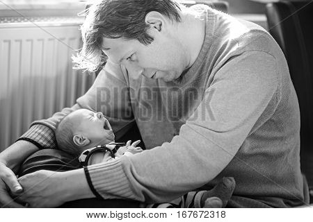 Happy proud young father having fun with newborn baby daughter, family portrait togehter. Dad with baby girl, love. New born child looking on dad. Bonding, family, new life. In black and white