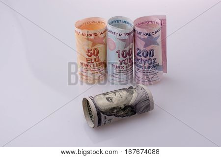 American dollar banknotes and Turksh Lira banknotes side by side on white background