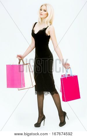 pretty girl or cute woman with long platinum blonde hair and fashionable makeup on face in sexy glamour black dress and shoes with pink shopping bags isolated on white background