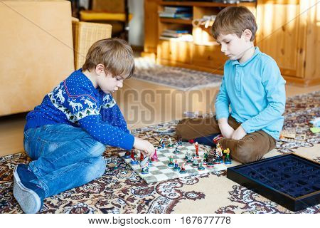 Two little kid boys playing chess game at home. children having fun with knight and soldier figures. Kid learning and thinking. Educational leisure at home. Siblings and best friends