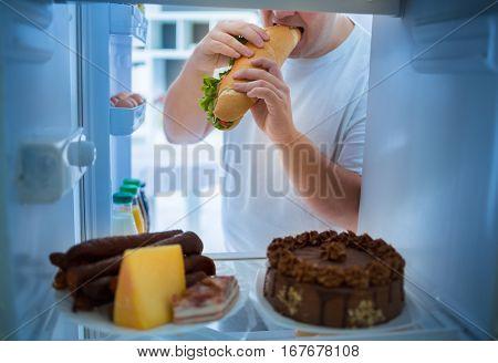 Overweight man on diet break diet with big sandwich roll