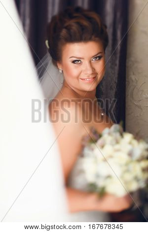 Joyful bride stand behind a window in the room