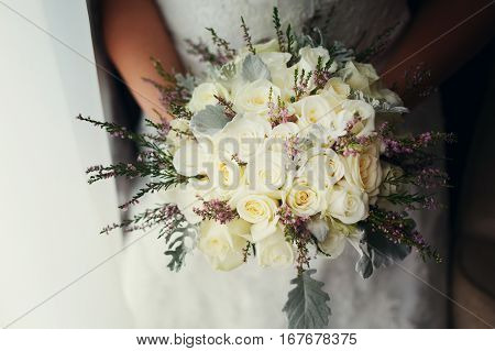 Bride holds a bouquet of lavander and white roses