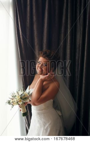 Smiling Bride Adjust An Earring Standing Behind A Big Window
