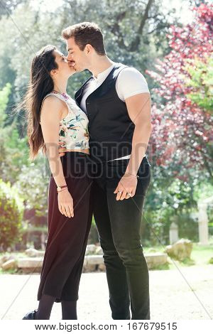 Beautiful couple embrace and kissing. Loving relationship and feeling. A men and a women is strongly embrace with passion and feeling. Behind them a natural park with trees and colorful foliage. Bright light that illuminates the scene.