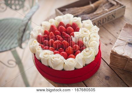 Valentine's Day background. The box of heart-shaped fresh strawberries with flowers