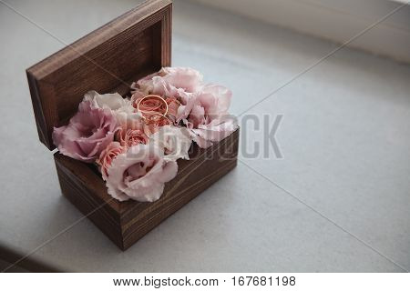 Top view shot of two gold wedding rings on rose flowers in old rustic wooden box for wedding ceremony. Festive decoration for wedding celebration.