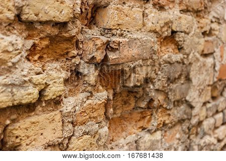 Damaged old wall. Texture of aged bricks. Time is ruthless.