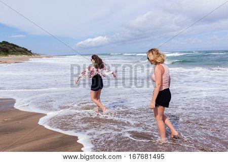 Girls holidays walking beach ocean waterline coastline.