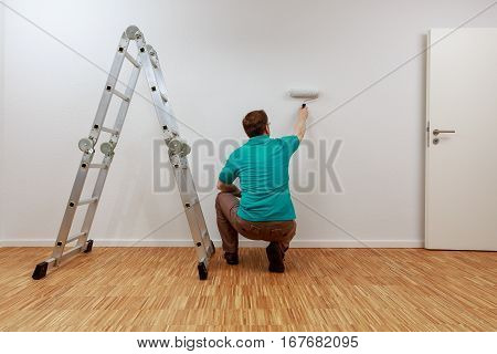 Man is painting a wall white.  He stand beside a ladder.