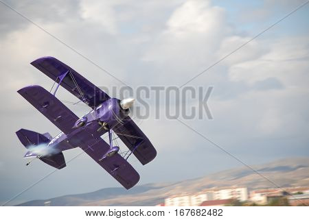 ANKARA, TURKEY - OCTOBER 11, 2008 : Airshow pilot Ali Ismet Ozturk and his purple violet PITTS aircraft over the Etimesgut Turkkusu Airport during the air fest of Turkish Air Association.