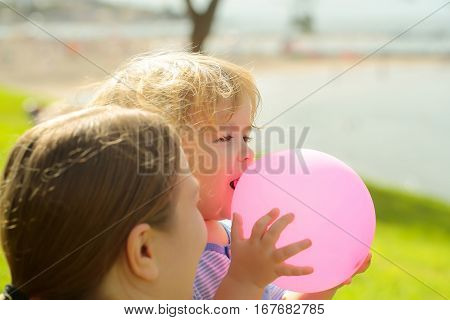 Mother and son cute baby boy with blond hair play with pink toy balloon on green grass by sea on sunny summer day on natural background at mothers day