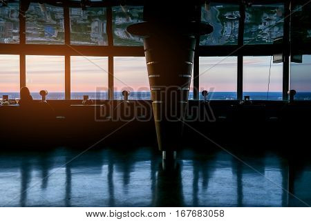 Sunset behind restaurant windows. Small tables and sofas. Romantic atmosphere and great view.