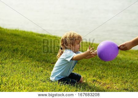 Cute Baby Boy Catches Violet Toy Balloon