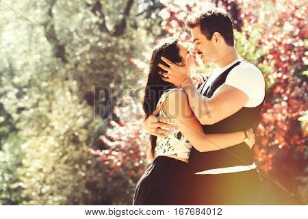 Passion and love. Couple kissing. Harmony, tenderness, peace and love between two lovers. Young men and young women embracing outdoors. Intense feeling and fiery passion. Bright light behind.
