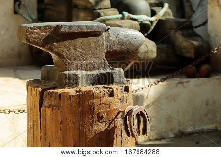 Old rugged iron anvil forging tool of blacksmith for metal works on wooden stool with rusty metal horseshoes on ancient smithy background
