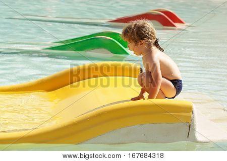 Happy Cute Baby Boy Plays On Yellow Waterslide