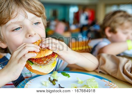 Cute healthy preschool kid boy eats hamburger sitting in school or nursery cafe. Happy child eating healthy organic and vegan food in restaurant. Childhood, health concept
