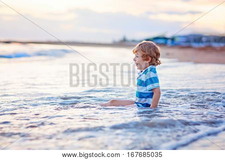 Funny little blond kid boy having fun with playing in wafes on the beach of ocean or see by sunset. Happy joyful child spending active vacations.