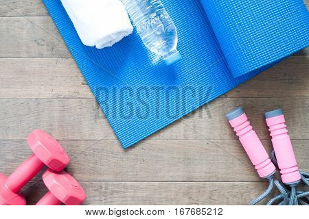 Flat lay of red dumbbells and sport equipment on wood background. Sport accessories Sport equipment top view