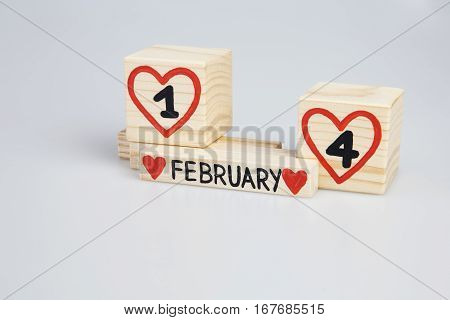 Valentine's day. Wooden cubes with handwritten one and four inside red hearts, February month. Copy space.