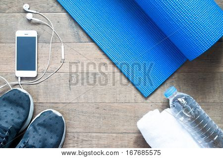 Flat lay of mobile phone with earphone and sport equipment on wood background. Sport accessories Sport equipment top view