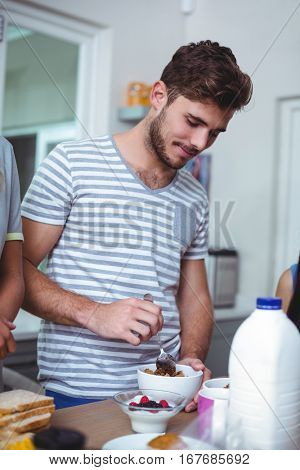 Smiling man preparing breakfast while standing at table