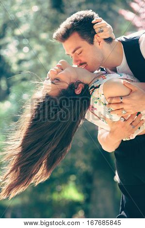 Seduction love, couple romantic relationship. Woman and man. Conquer a happy woman. A romantic man embracing and kissing a smiling woman. Outdoors with trees and flowers in the background.