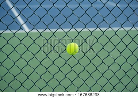 Tennis Ball On Metal Wire Against Tennis Court. Concept Of Tennis Protection Equipment