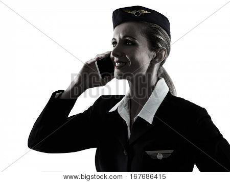 one caucasian Stewardess cabin crew  woman on the phone isolated on white background in  silhouette