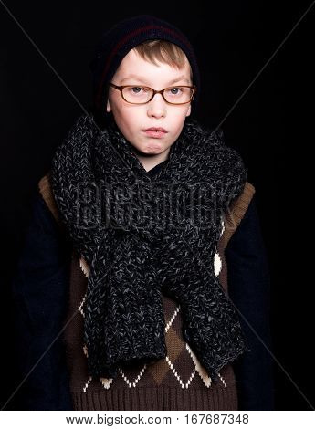 small boy or cute nerd kid in glasses hat and fashionable knitted scarf on black background