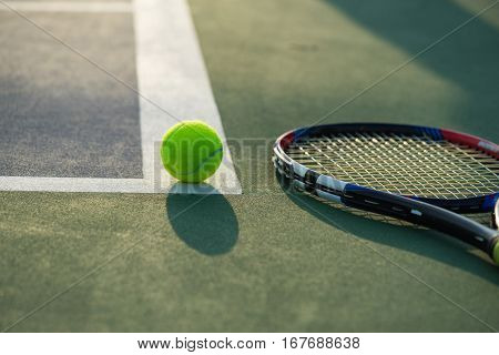 Tennis Ball And Racket Under Late Evening Sunlight