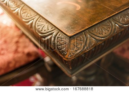 Corner of old wooden table. Brown wood with carved ornament. History of art.