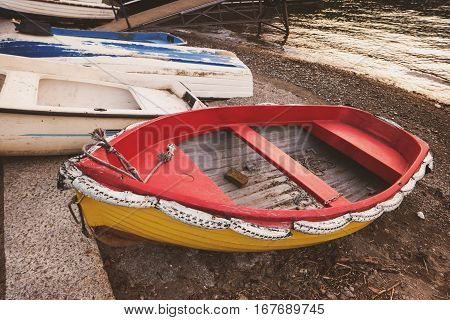 Boats on lake shore. Bright-colored row boat. Moor to an island.