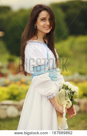 Stunning Brunette Girl In An Embroidered Blue And White Dress Holds A Bouquet Of Little White Roses