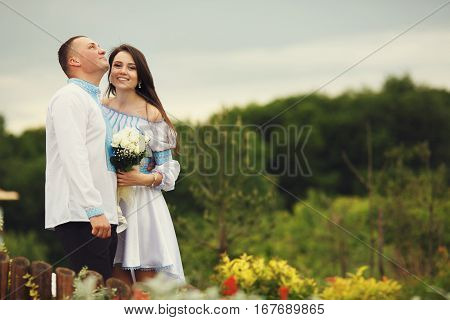 Amazing Bride In An Embroidered Dress Smiles Standing Behind A Groom On The Green Field