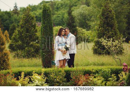 Groom Holds Bride's Shoulder Tenderly Standing Between Bushes In The Park
