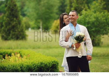 Bride Hugs From Behind A Groom In An Embroidered Blue Shirt